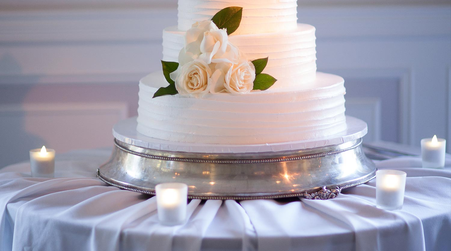 Photo: close up clean white wedding cake with white flowers