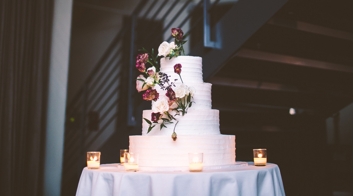 Photo: white frosted wedding cake, flowers and leaves sticking out of the four tiers