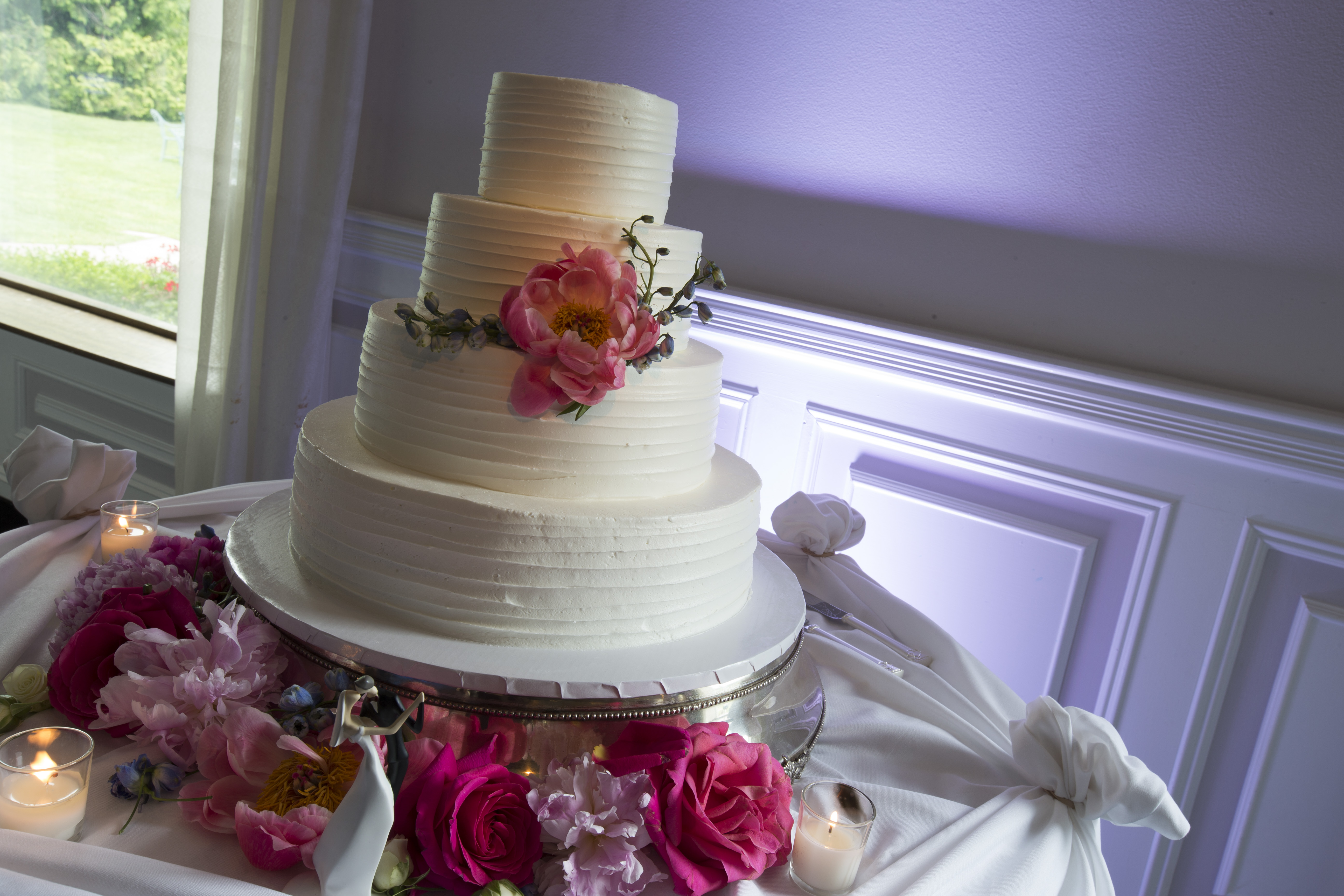 Photo: four tier clean white frosted cake with large pink flower