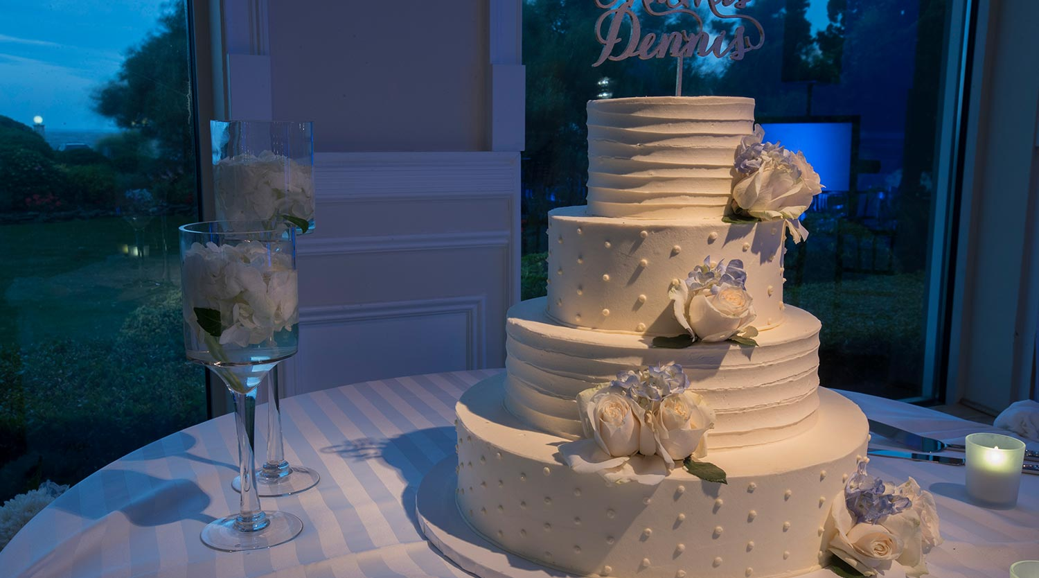 Photo: four tier wedding cake with alternating frosted pattern and white flowers