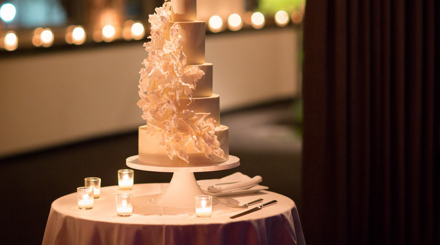 Photo: five tier smooth white wedding cake with cascading flowers