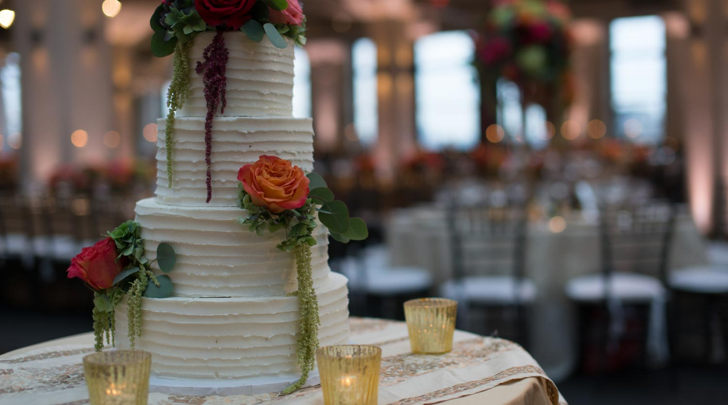 Photo: white frosted wedding cake with real flowers and hanging leaves