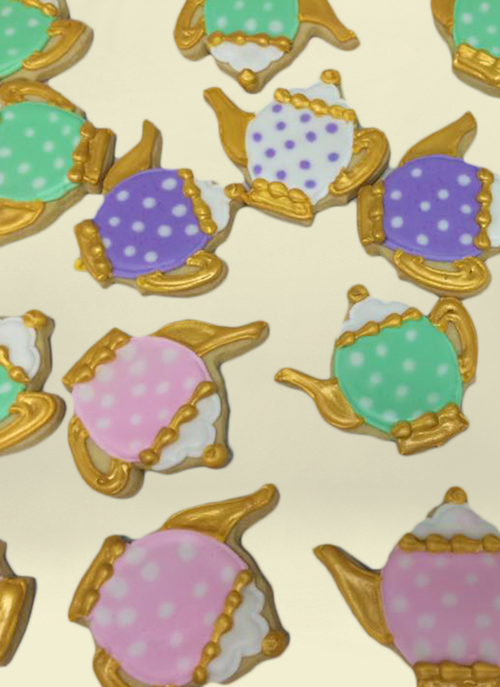 Photo: cookies shaped like tea pots and gold royal ice with dot pattern
