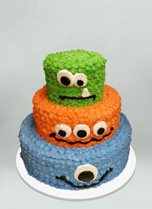 Photo: 3 tire frosted green, orange, blue cake with monster face on each tier