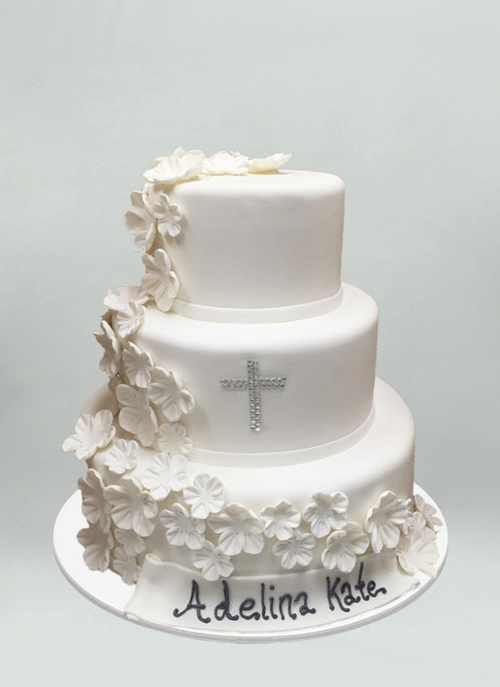 Photo: white fondant cake with cascading white sugar flowers and gem cross