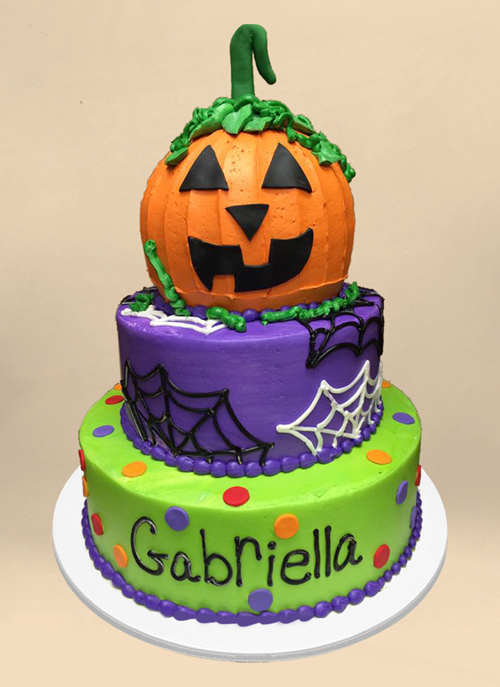 Photo: frosted green and purple cake with piped spider webs and large jack-o-lantern shaped top tier