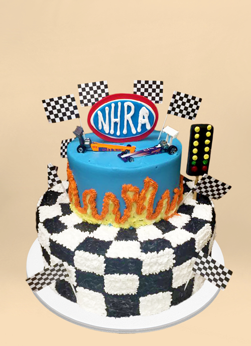 Photo: frosted cake with checkered pattern and flags, nascar cars on top