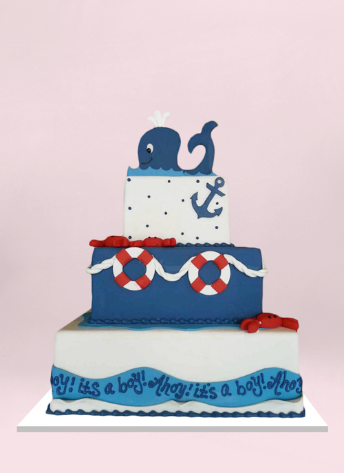 Photo: 3 square fondant tiers with with nautical elements and a smiling whale topper