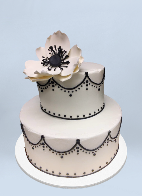Photo: white frosted 2 tier cake with black piping and large white sugar flower