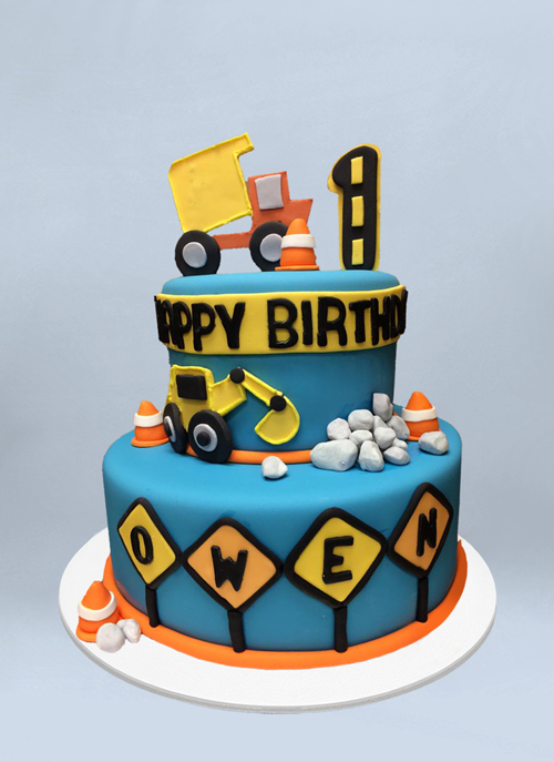 Photo: fondant cake with fondant construction cones, rocks, trucks and signs around the tiers